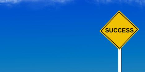 Yellow sign reading SUCCESS against a bright blue sky