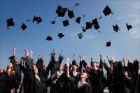 college students celebrating graduation by throwing mortarboards up in the air