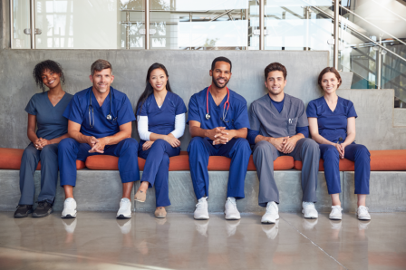 Row of smiling medical students sitting on a bench at a hospital