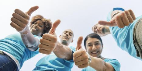 Group of 4 employees wearing blue shirts posing with thumbs up