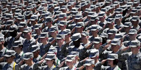 Rows of soldiers standing at attention, saluting their leader