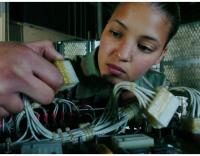 Female technician fixing control panel