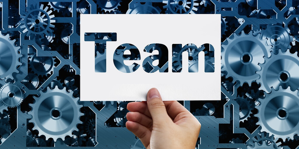 Team stencil held overa set of complicated gears