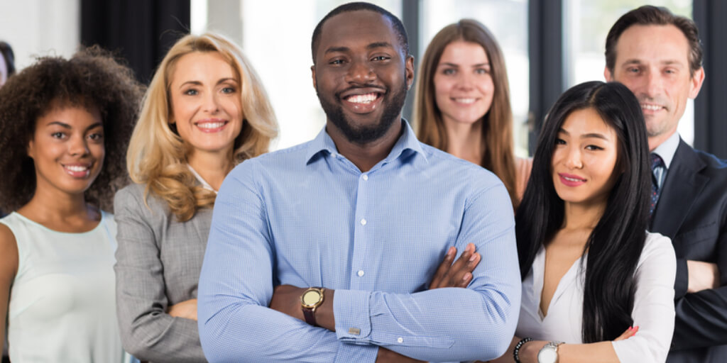 Smiling boss surrounded by group of happy employees