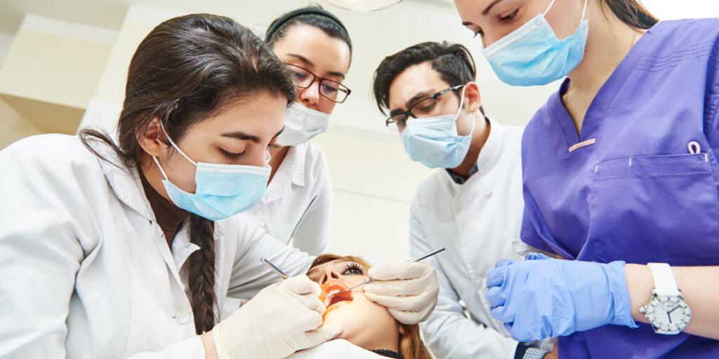 Dental students observing dentist working on patient