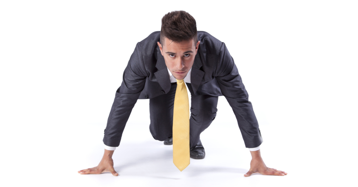 Youn man in suit and yellow tie getting ready to sprint