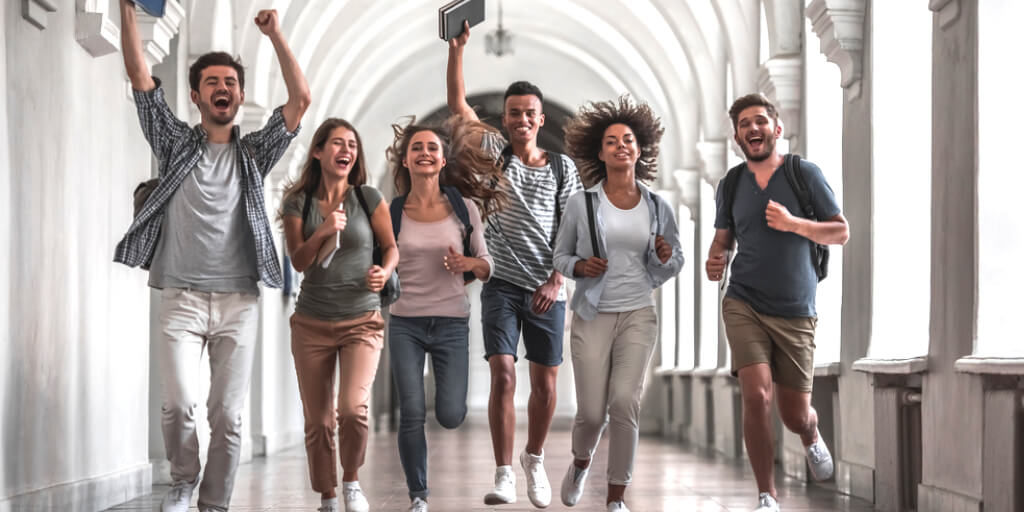 6 college students running down a hallway celebrating success