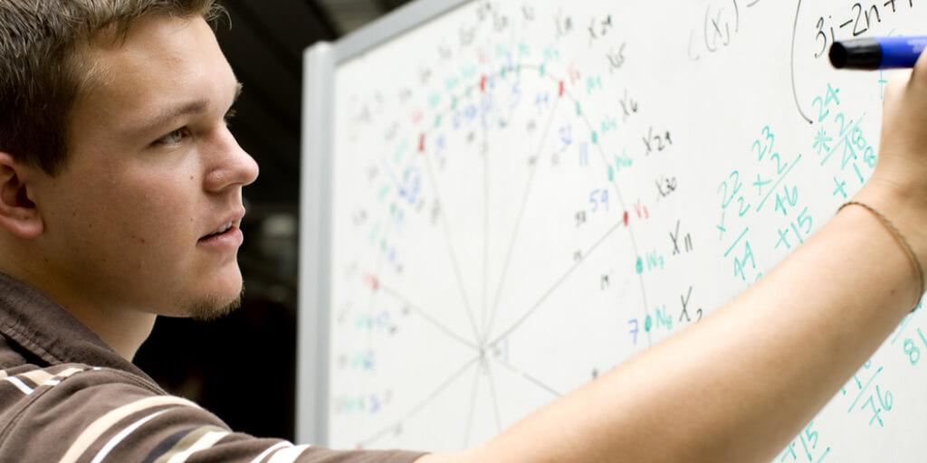 Tenn age boy writing equations on a white board