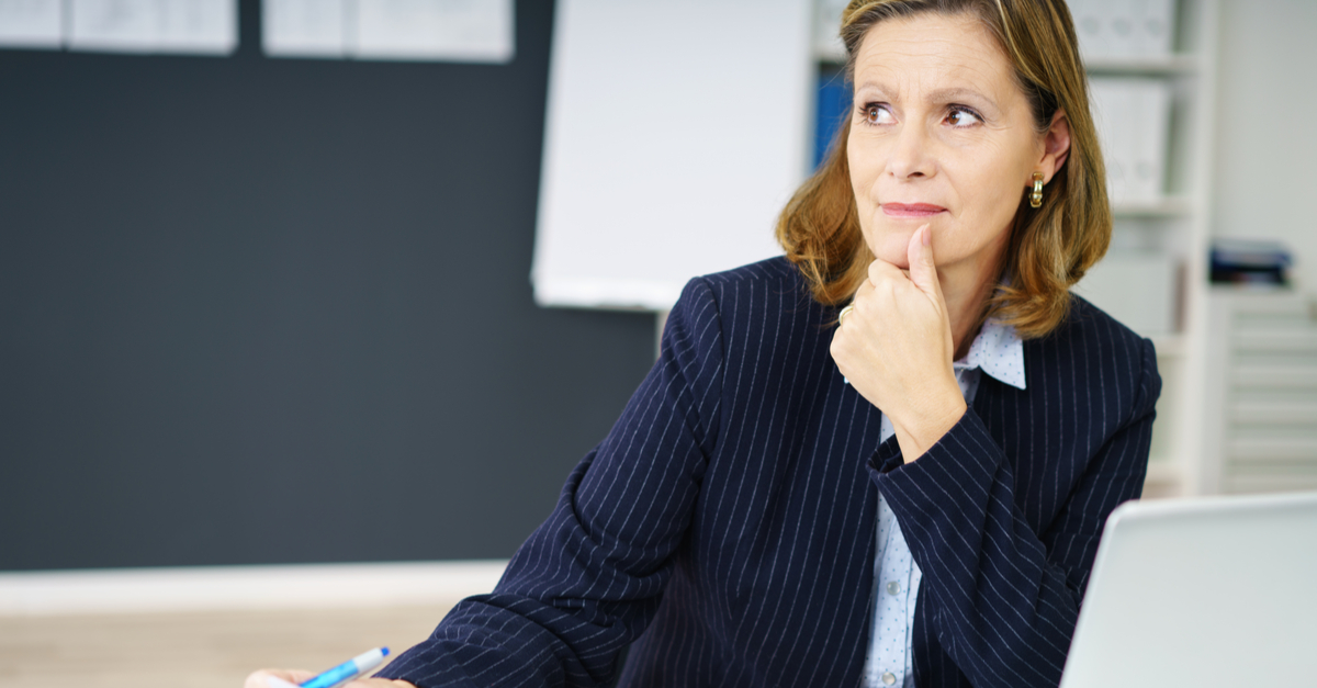 Female executive sitting at her desk thinking about honesty
