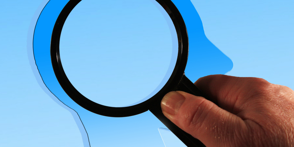 Hand holding a magnifying glass over the blue silhouette of a head on a blue background
