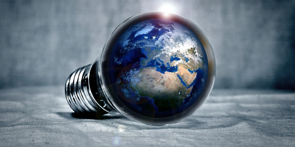The power of ideas represented by a light bulb reflecting the image of the globe